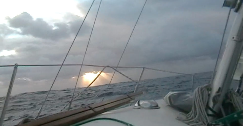 A photograph showing the sun rising on the horizon off the bow of the S/V Pestilence