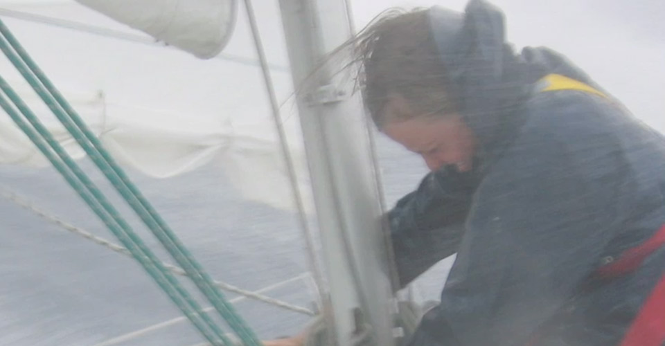 An image depicting a closeup of a person sailing in rough seas